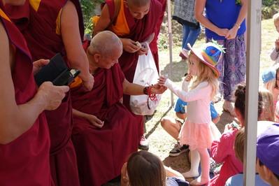 Lama Zopa Rinpoche gives a toy koala to a child at Chenrezig Institute, Australia, Sept. 2014. Photo: Ven. Roger Kunsang.