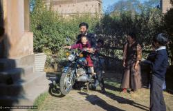 (09619_sl.JPG) Jampa Trinley and Daja Meston (Thubten Wangchuk) on a motor cycle, at their house in Kathmandu, Nepal, 1975. Kelsang Puntsog Rinpoche, the son of Lama Yeshe's old friend Jampa Trinley, was later recognized to be the reincarnation of Geshe Ngawang Gendun, one of Lama's teachers.