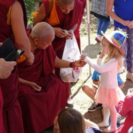 Lama Zopa Rinpoche gives a toy koala to a child at Chenrezig Institute, Australia, Sept. 2014. Photo: Ven. Roger Kunsang.